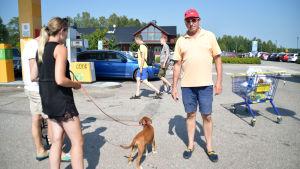 människor och en hund vid en bensinstatione