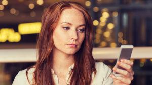 Kvinna tittar fundersamt på sin smarttelefon