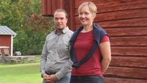 Annika Holmén och Tommy Friman står framför en rödmålad ladugårdsvägg i ett soligt sensommarväder.