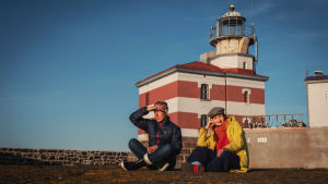 En man och en kvinna sitter på klippa med benen i kors, i bakgrunden rödvitrandig fyr.