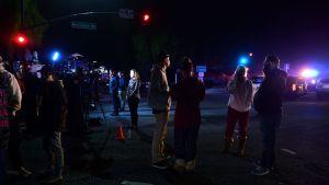 Personer står och följer med situationen efter masskjutningen