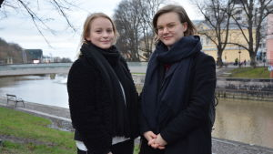 Sofia Haapala och Cecilia Pahlman i svarta rockar ser mot kameran, de står intill en höstig aura Å.