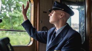 Junankuljettaja univormussaan heilauttamassa kättään junan ikkunassa.