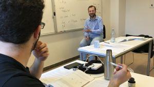 Lärare framför whiteboard med dansk text förklarar något för en elev.