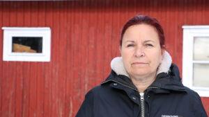 En kvinna med rödbrunt hår står framför en röd träbyggnad.