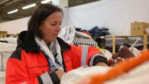 Cati Huhta tittar ner i en säck med gamla textiler