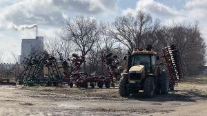 Traktor på bondgård i Kansas i solsken, gödselfabrik med skorsten i bakgrunden.