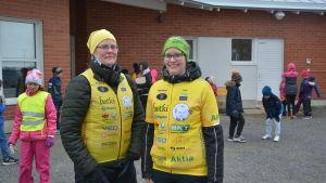 Två kvinnor i gula västar utanpå sina vanliga kläder, barn i bakgrunden.