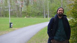 Tiago Martins Pinto står med ansiktet mot kameran vid en buske i en park.
