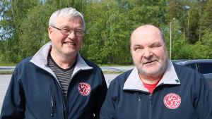 Två medelålders män står på en parkeringsplats.