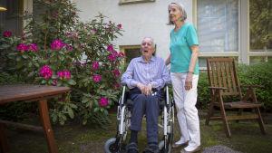 Irmeli och Heikki Laajanen utanför ett vårdhem. Heikki sitter i rullstol och Irmeli tittar på honom och håller handen på hans rygg. Bakom dem finns en blommande buske och utomhusmöbler.