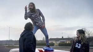 Pappan (Mattias Sivell) står på en bil och sjunger, Saga och Gösta står och ser på.