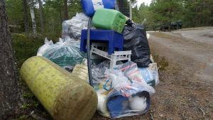 En stor plasthög i skogen. I högen finns påsar, plastbackar nät, dunkar och mycket anant skräp.