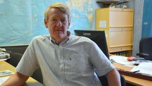 En man med blårandig skjorta sitter i ett kontor.