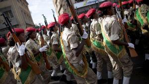 Soldater med röda baretter marscherar på en gata. I handen har de gevär som pekar rakt uppåt. Stämningen verkar uppspelt men ändå glad.
