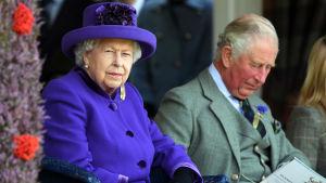 Drottning Elizabeth sitter bredvid prins Charles. Hon iklädd en lila rock med tillhörande hatt och han med en grå kostym.