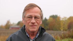 En man med kort, lite gråaktigt hår och glasögon står framför en åker.