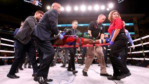 Boxaren Patrick Day bärs ut på bår, han om ges av flera personer.