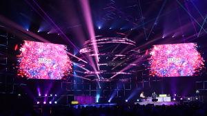 En scen i ett mörkt utrymme som genomkorsas av lila laserljus.