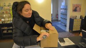 Kvinna öppnar en låda.