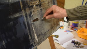 En hand som målar vitt på en blå tavla.