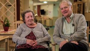 äldre par sitter och småler