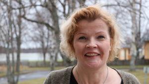 En kvinna i 50-årsåldern med axellångt rödbrunthår ler. I bakgrunden syns träd.