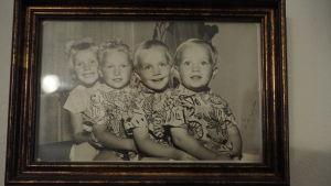 fyra ljushåriga glada barn sitter i kö med armarna runt varandra på svartvitt fotografi i ram