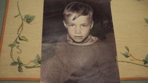 Liten, allvarlig, litet lockig pojke på svarvitt fotografi.