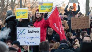 Personer håller upp plakat och demonstrerar i Tyskland.