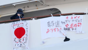 """En passagerare ombord på Diamond Princess hänger upp ett lakan med texten """"allvarlig brist på mediciner."""""""