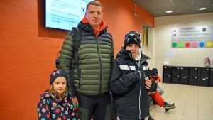 En man och två barn i ytterkläder står inne i aulan till Borgå simhall. De ser in i kameran.