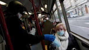 En polis delar ut ansiktsmasker till arbetare som måste på jobb i Spanien trots coronavirusåtgärderna.