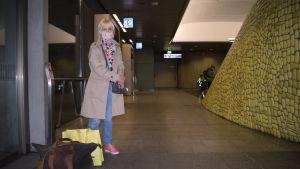 Marja Alasma väntar på sin buss. Hon bär munskydd.