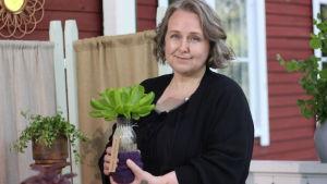 En kvinna håller upp en glasflaska med sallad i.