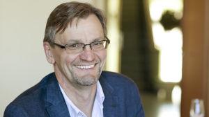 Professorn i internmedicin vid Helsingfors universitet Per-Henrik Groop leende i blå kavaj.