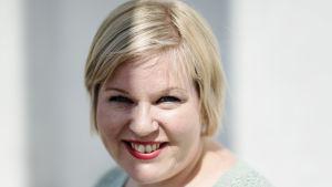 Annika Saarikko tittar lite uppåt och in i kameran. Hon ler.