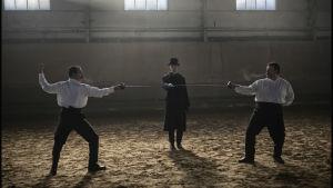 Två män med vita skjortor står beredda att fäktas. En svartklädd man står i mitten.