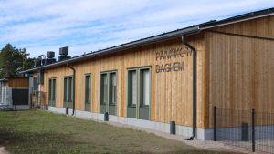 En träbyggnad. Texten päiväkoti daghem syns tydligt på fasaden.