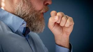 En skäggig man hostar med handen framför munnen.