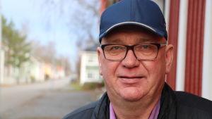 En man med glasögon och keps står intill en husvägg.