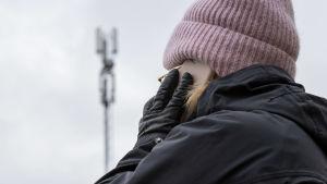 Kvinna utomhus, talar i mobiltelefon. I bakgrunden skönjer man en mobilmast.