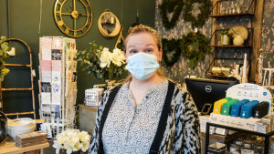 Kvinna i munskydd står inne i inredningsbutik.