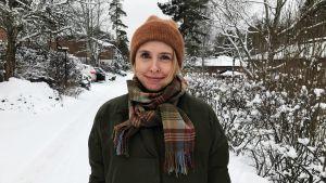 En kvinna med ljust hår står i ett vinterlandskap och ler in i kameran