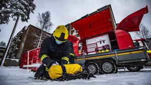 En brandman med gul hjälm sitter på den snöiga marken och gör sin gula tryckluftsflaska färdig för rökdykning. Bakom honom står en röd brandkårsvagn med utrustning parkerad.