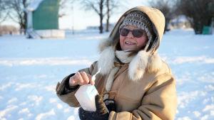 kvinna i vinterkläder som håller på att ta fram ett istegel ur ett mjölkpaket
