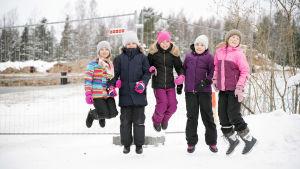 barn hoppar framför skolbygge