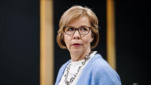 Kvinna med blå tröja och glasögon mot en svart bakgrund.