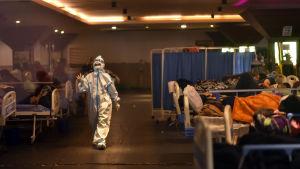 En skyddsdräktsklädd skötare går igenom en tillfällig sjukhusavdelning.