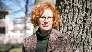 En kvinna med rött lockogt hår står ute lite lutad mot trädstam.